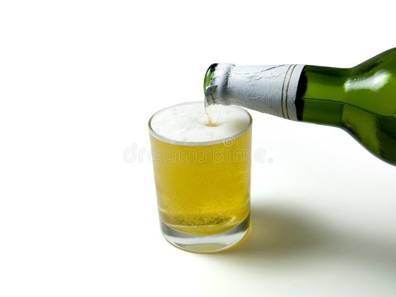 Birra che versa giù da una bottiglia fotografia stock libera da diritti