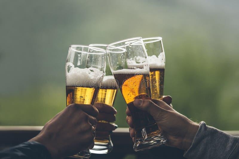 Birra con i ragazzi alti della luce della schiuma nelle mani degli amici che alzano a fotografie stock