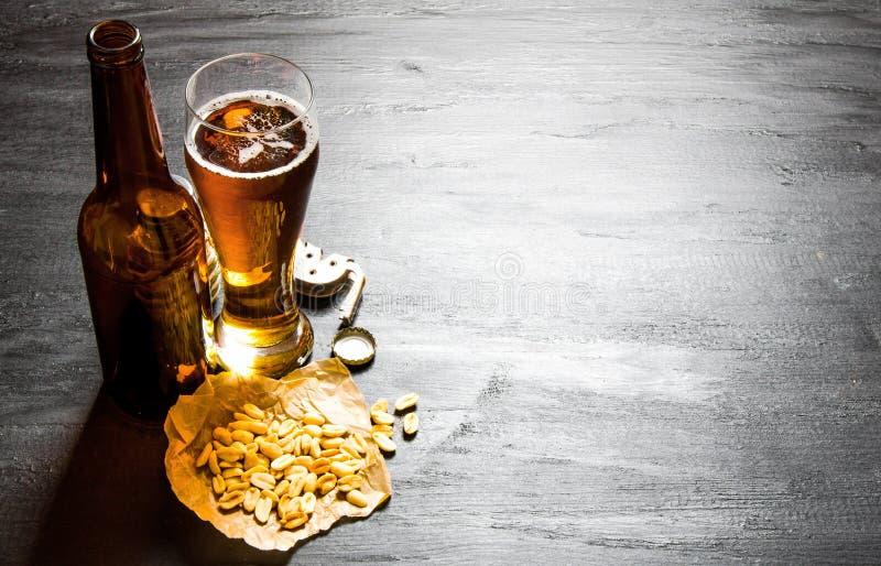 Birra con le arachidi sulla tavola di legno nera Spazio libero per testo immagini stock libere da diritti