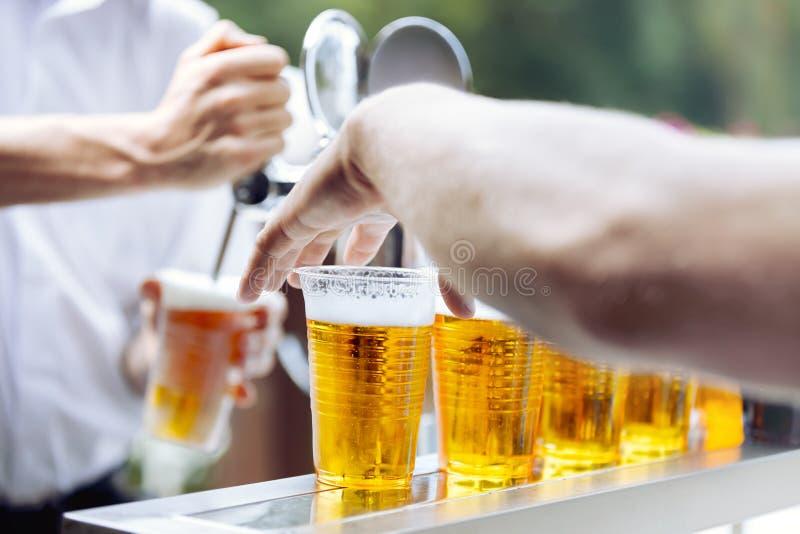 Birra del disegno dell'uomo La mano prende la tazza della plastica della birra fotografie stock