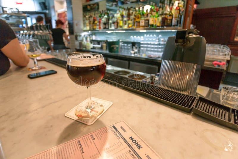 Birra del mestiere in vetro dentro la barra sul contatore con i bevitori e gli ospiti fotografia stock
