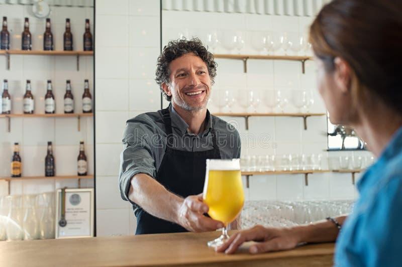 Birra del servizio del barista alla donna immagini stock