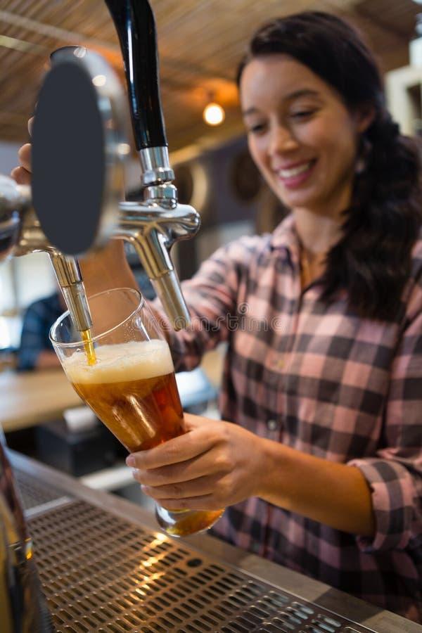 Birra di versamento della cameriera al banco graziosa dal rubinetto in vetro fotografie stock
