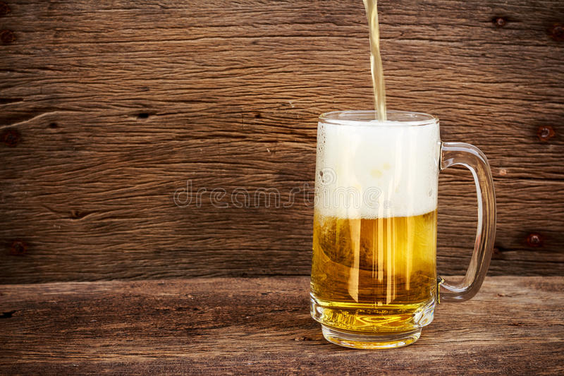 Birra di versamento nel vetro fotografia stock