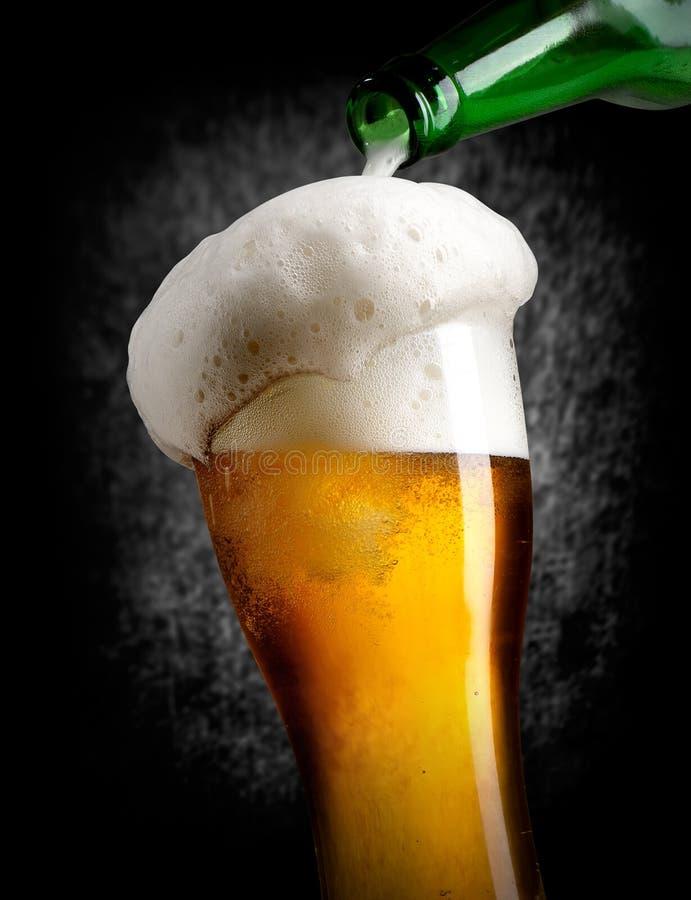 Birra di versamento sul nero fotografia stock libera da diritti