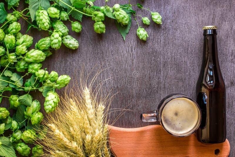 Birra di vetro e della bottiglia con fare gli ingredienti Fiore del luppolo con grano Vista superiore fotografia stock
