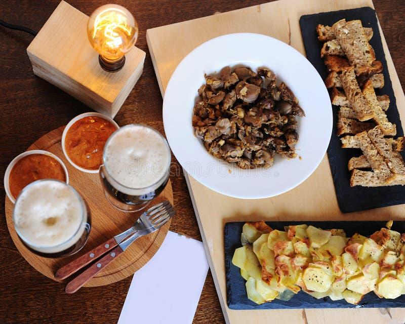 Birra e spuntini Lampada di Edison Natura morta dei pantaloni a vita bassa Una scheda di avviso Patatine fritte, fritture Spine d fotografie stock