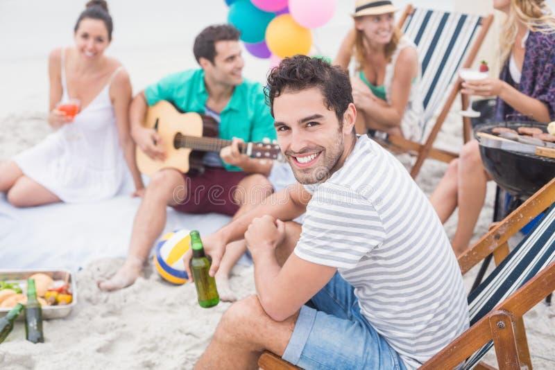Birra felice della tenuta dell'uomo e sorridere mentre sedendosi con i suoi amici immagine stock libera da diritti