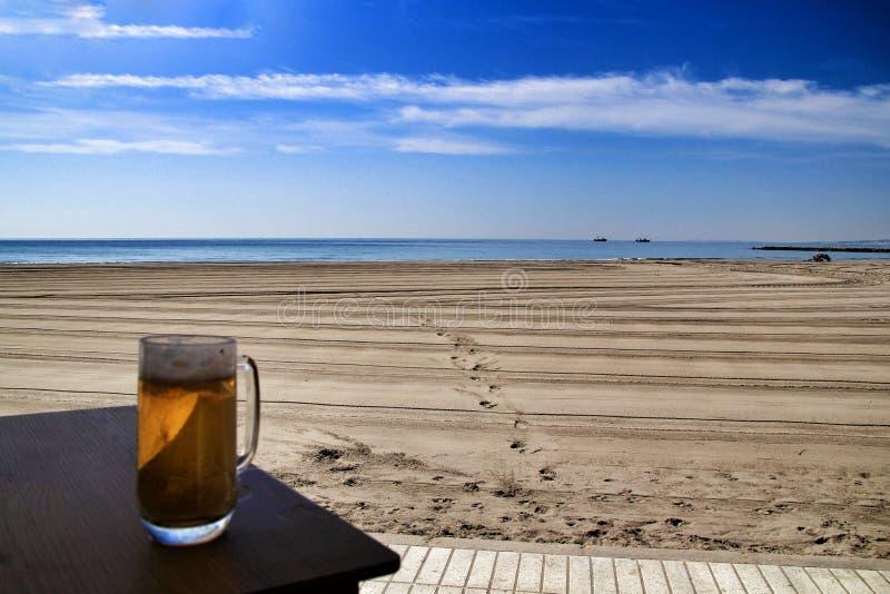 Birra fredda sul terrazzo di una barra della spiaggia fotografia stock