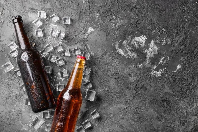 Birra fresca in bottiglie di vetro e cubetti di ghiaccio su fondo grigio fotografie stock libere da diritti