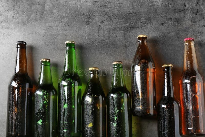 Birra fresca in bottiglie di vetro su fondo grigio immagine stock libera da diritti