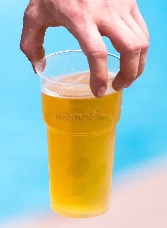 Birra fresca in una tazza di plastica nella mano immagini stock