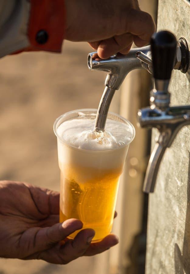 Birra fresca in una tazza di plastica nella mano fotografia stock libera da diritti