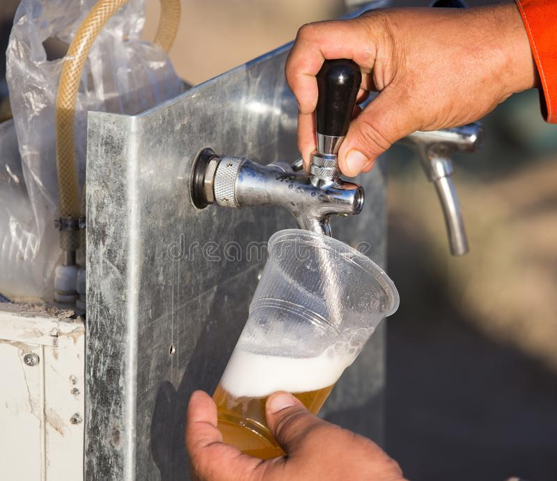 Birra fresca in una tazza di plastica nella mano immagine stock
