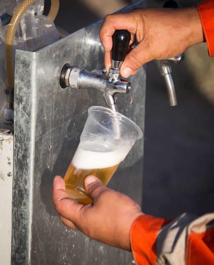 Birra fresca in una tazza di plastica nella mano immagini stock libere da diritti
