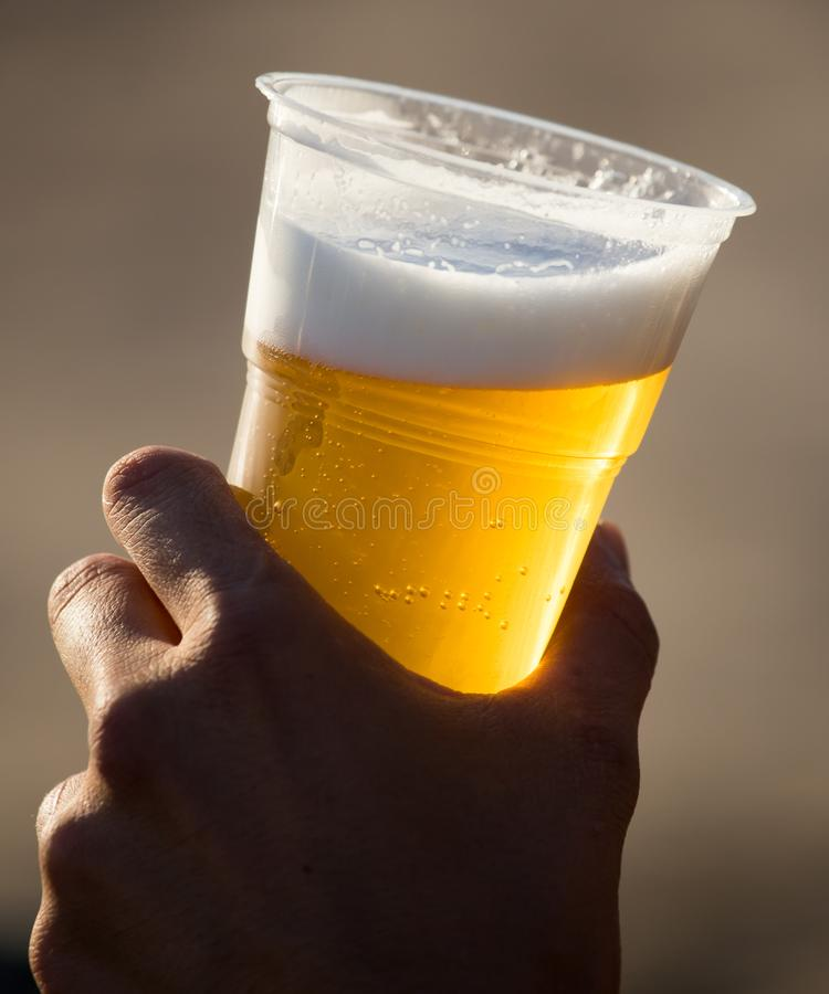 Birra fresca in una tazza di plastica nella mano fotografia stock