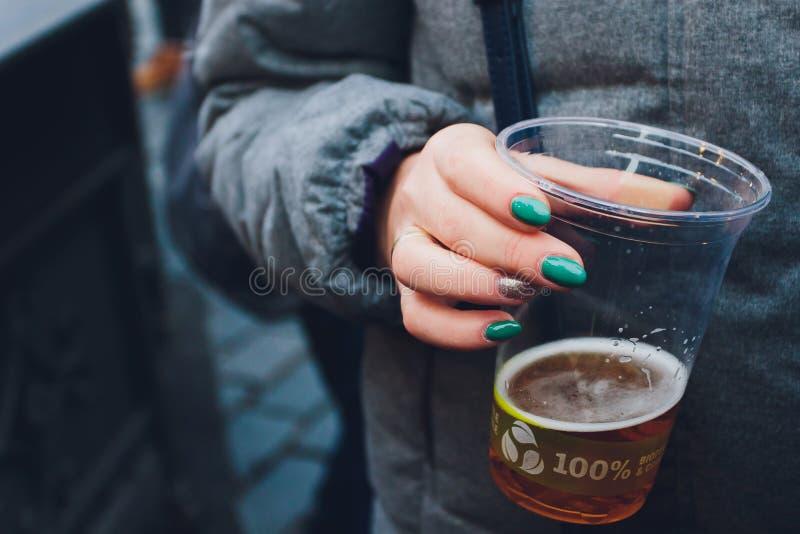 Birra fresca in una tazza di plastica nella mano immagine stock libera da diritti