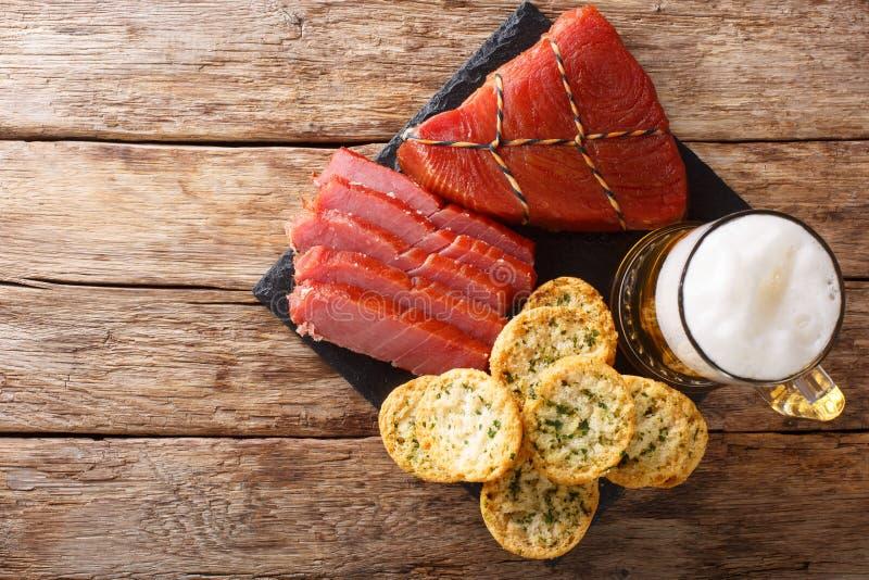 Birra leggera con schiuma, il tonno affumicato ed il pane tostato con aglio ed il primo piano di verdi vista superiore orizzontal fotografia stock