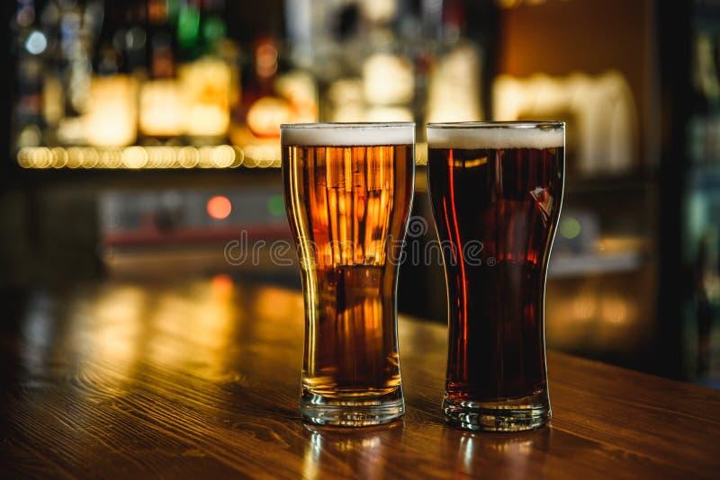 Birra leggera e scura su un fondo del pub immagine stock libera da diritti