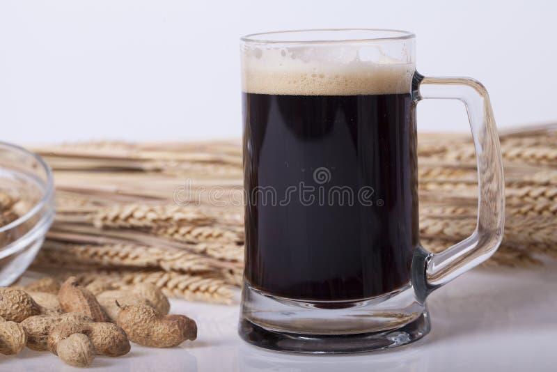 Birra nera nel vetro sulla tavola fotografie stock