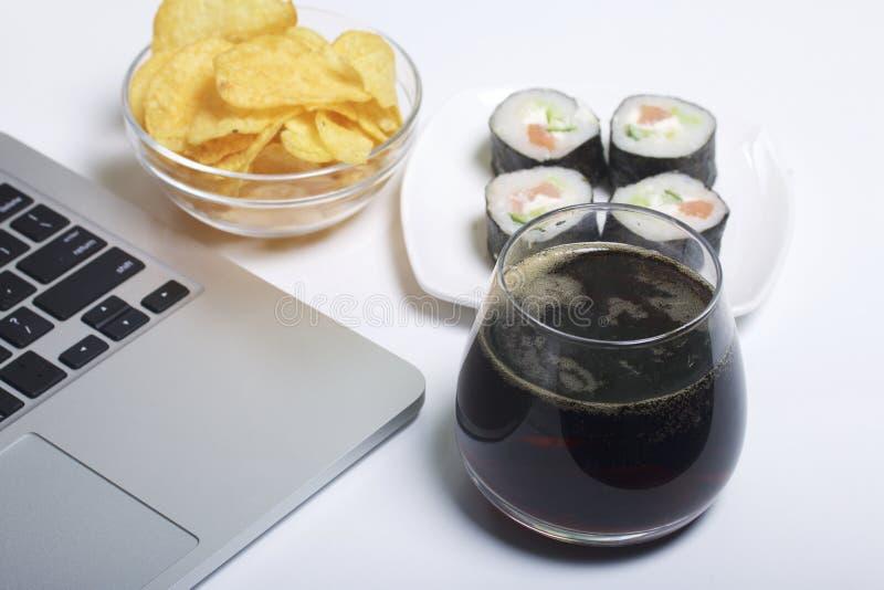 Birra, patatine fritte e sushi Supporto vicino al computer portatile Resto del giorno libero immagini stock
