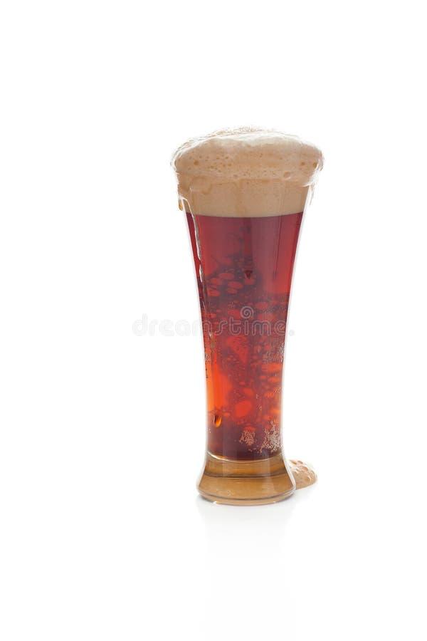 Birra scura con la gomma piuma in un vetro fotografia stock libera da diritti