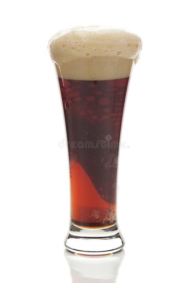 Birra scura con la schiuma in un vetro alto fotografia stock libera da diritti