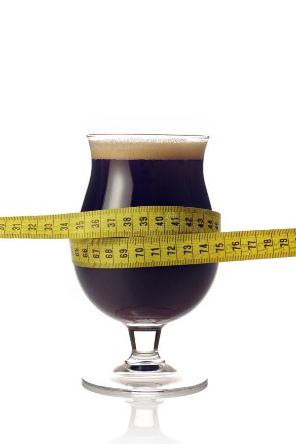 Birra scura con nastro adesivo di misura fotografia stock