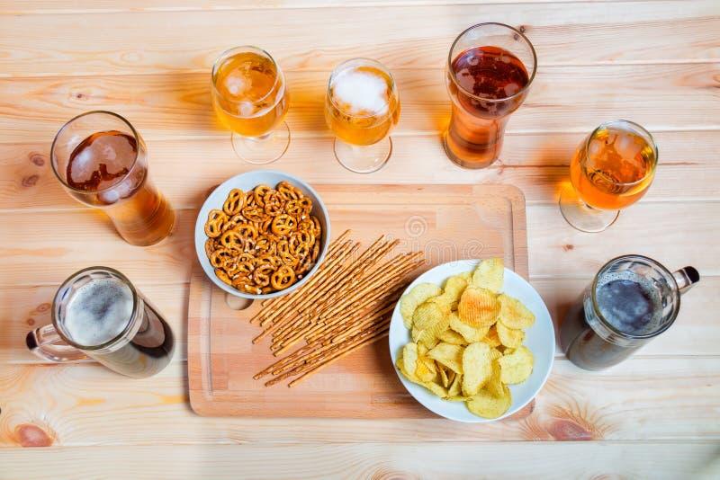 Birra sulla tabella di legno Gli spuntini della birra sono chip, paglie salate e ciambelline salate immagini stock