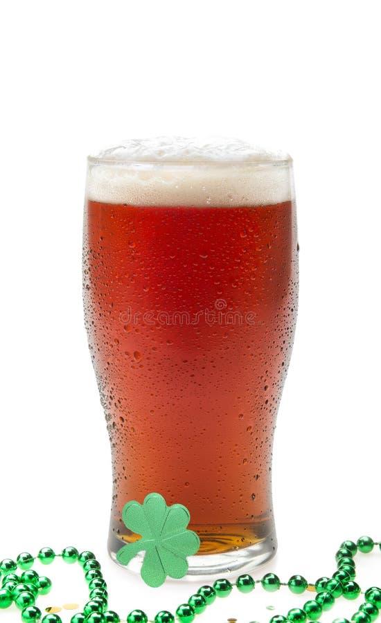 Birra in un vetro della pinta con le perle ed il trifoglio fotografia stock
