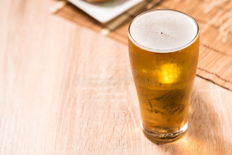 Birra in vetro ed hamburger sulla tavola di legno fotografia stock