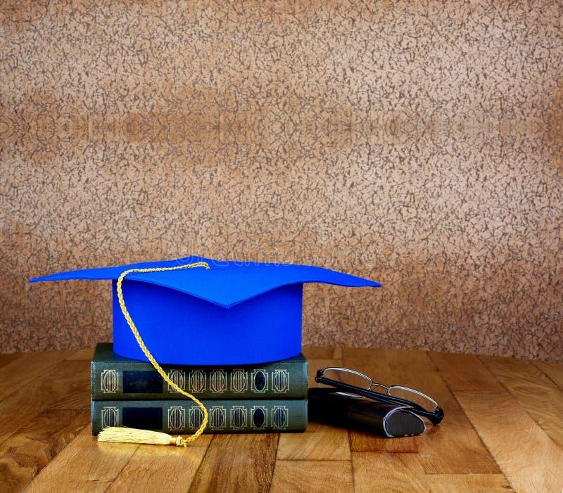 Birrete de la graduación encima de la pila de libros fotos de archivo libres de regalías