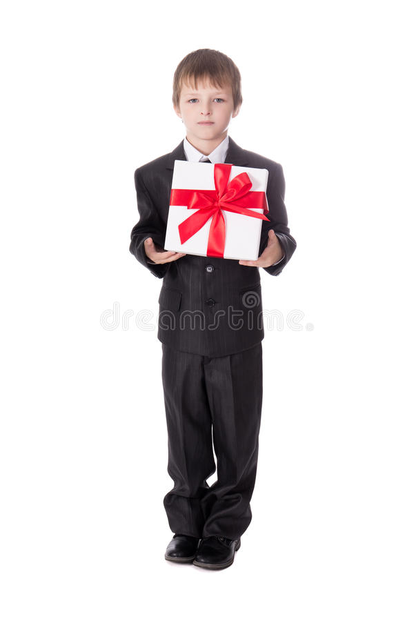 Birtday or christmas concept - little boy in business suit with. Gift box isolated on white background stock photography