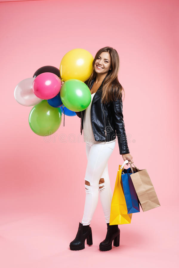 Birtday girl in amazing outfit looking straight holding gifts. Birtday girl in amazing outfit with ripped white jeans, ankle boots and black jacket stock images