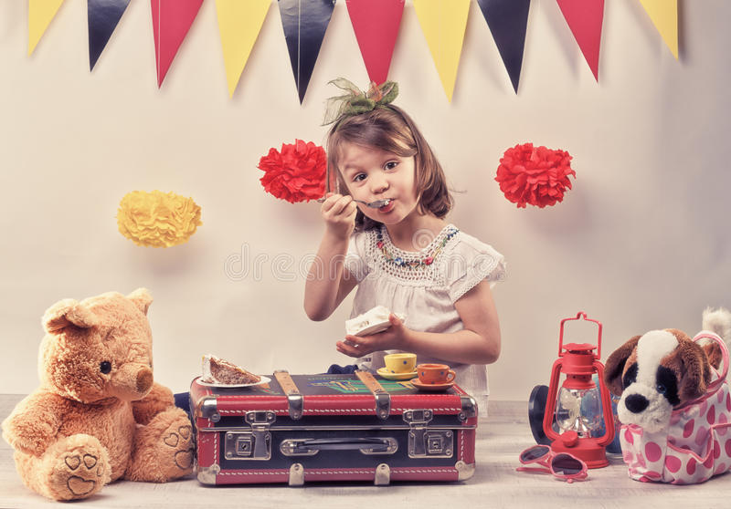 Birtday party with friends. Little girl eating a piece of cake on the suitcase with her friend the teddy bear. Red lantern, pampoms, and fanions are the picnic stock photo