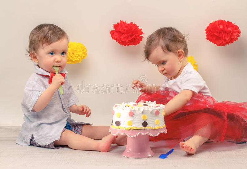 Birtday party. One-year-old twins on they birthday party with cake and wall decoration stock images