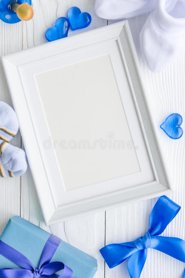 Birth of child - blank picture frame on wooden background stock photography