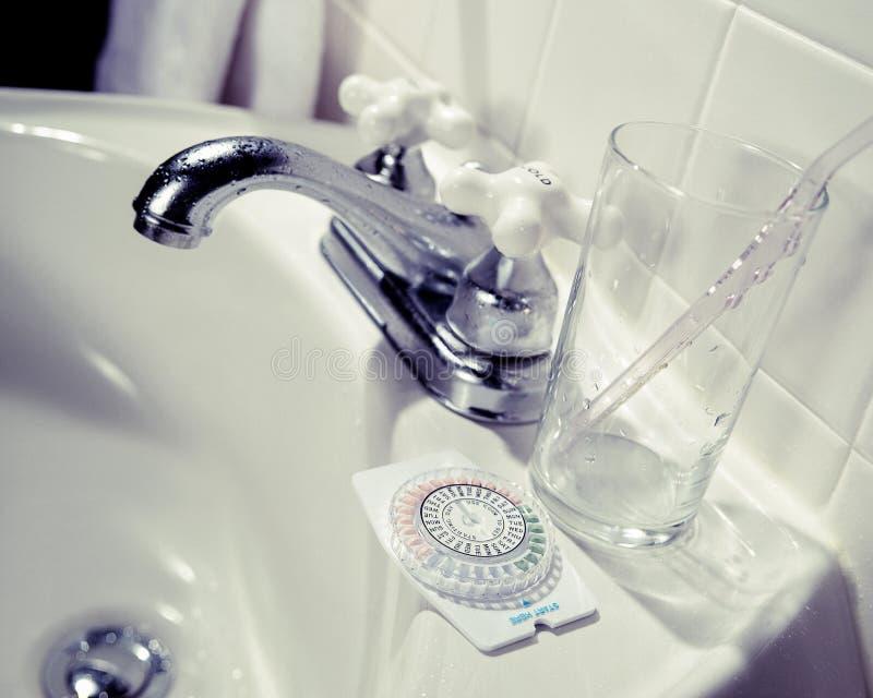 Birth control pills in dispenser on bathroom sink royalty free stock image