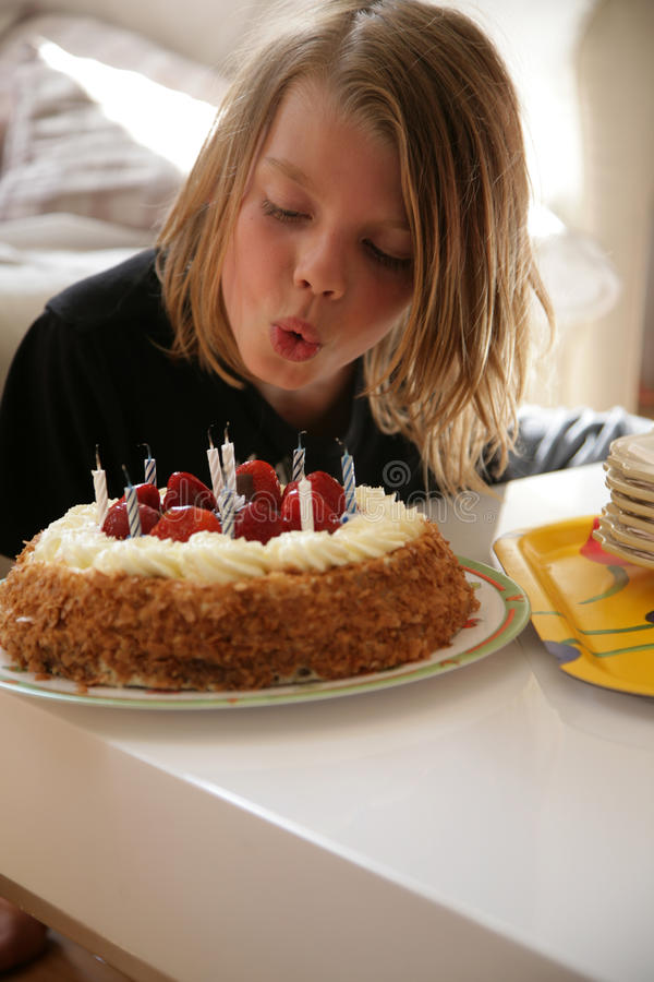 Birthday. Young boy,9 years old blow out candle on birthday cake stock photo