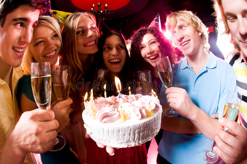 During birthday. Portrait of friends holding cocktails around festive cake during birthday royalty free stock photo