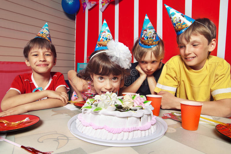 Birthday. Little girl going to eat cake in her birthday round about her friends royalty free stock images