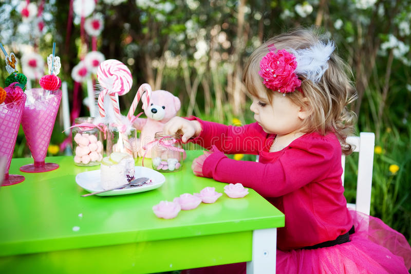 Birthday. Little girl is eating candies on her birthday royalty free stock photo