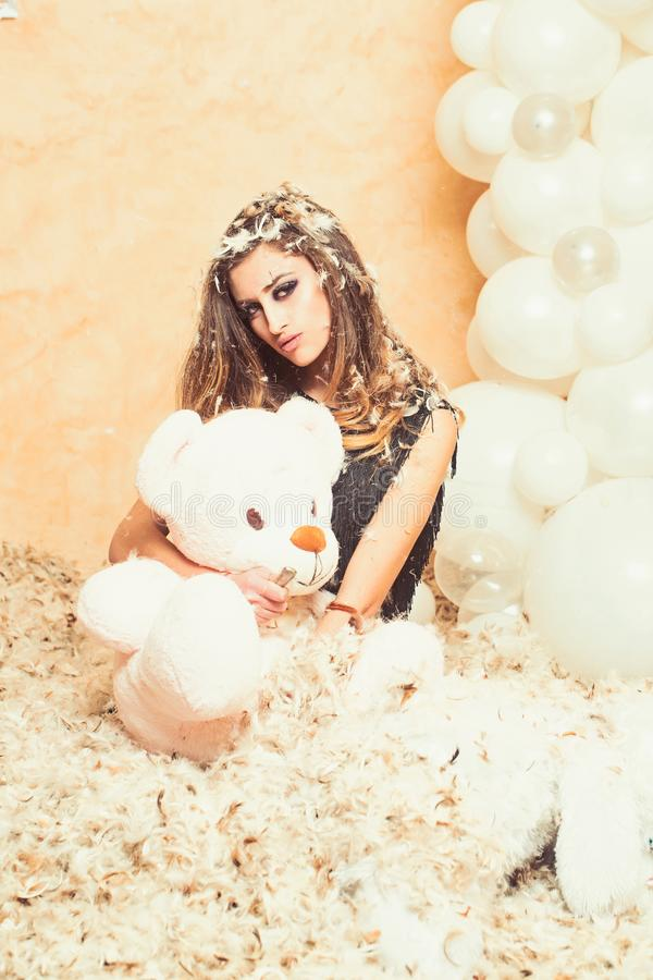 Birthday anniversary gift. Woman rip teddy bear with knife. Sensual woman and animal doll in feather snowflakes. Bad. Behavior and aggression concept stock photos