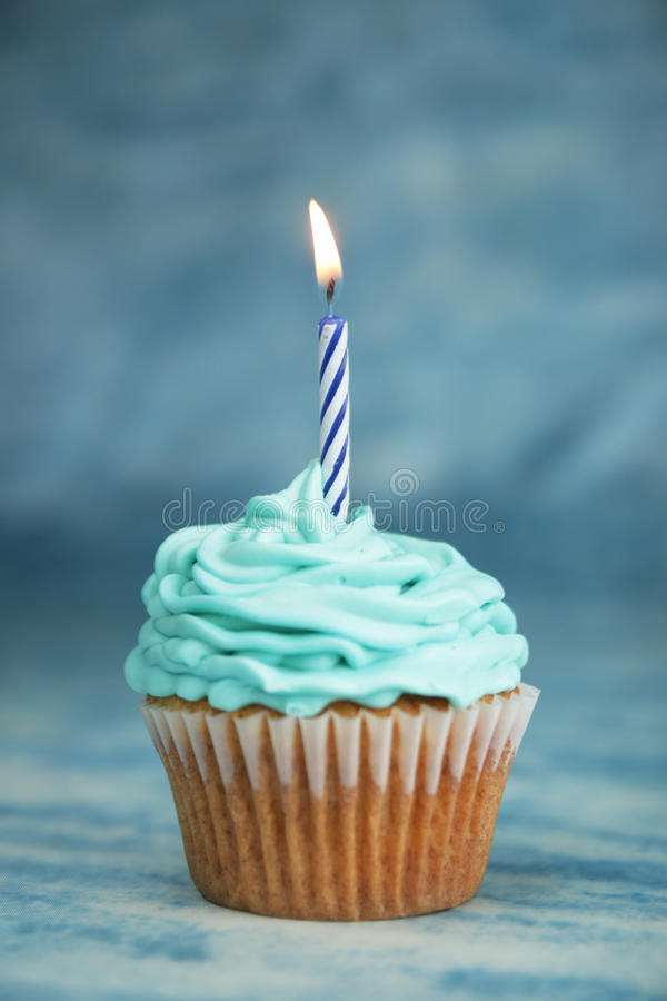 Birthday blue cake. Blue birthday cake with candle on a blue background stock image
