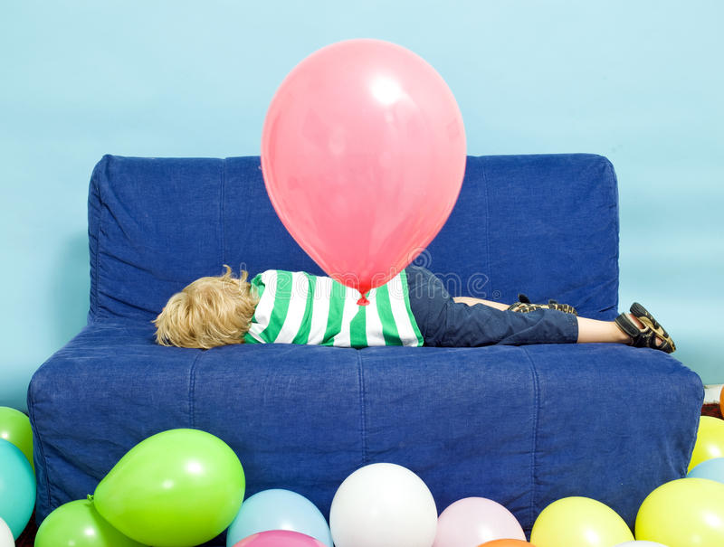 Birthday blues. Young Boy lying down on a couch on his birthday stock image