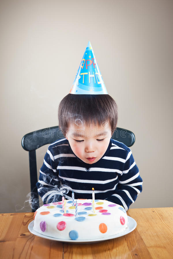 Birthday boy. A portrait of an asian boy blowing candles celebrating his birthday stock photography