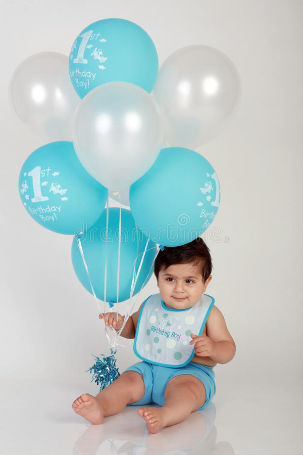 Birthday boy. Baby boy's 1st birthday portrait with plain white background and dozens of blue and white balloons royalty free stock image