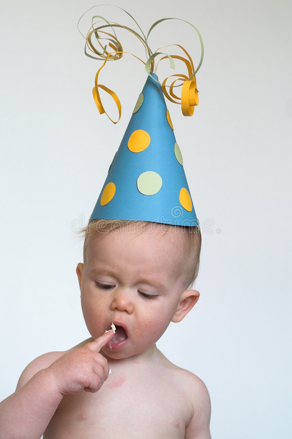 Birthday Boy. Image of an adorable 1 year old, wearing a paper hat, eating birthday cake royalty free stock photo
