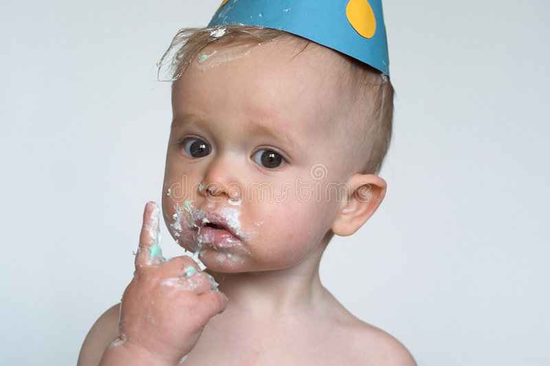 Birthday Boy. Image of an adorable 1 year old, wearing a paper hat, eating birthday cake royalty free stock image