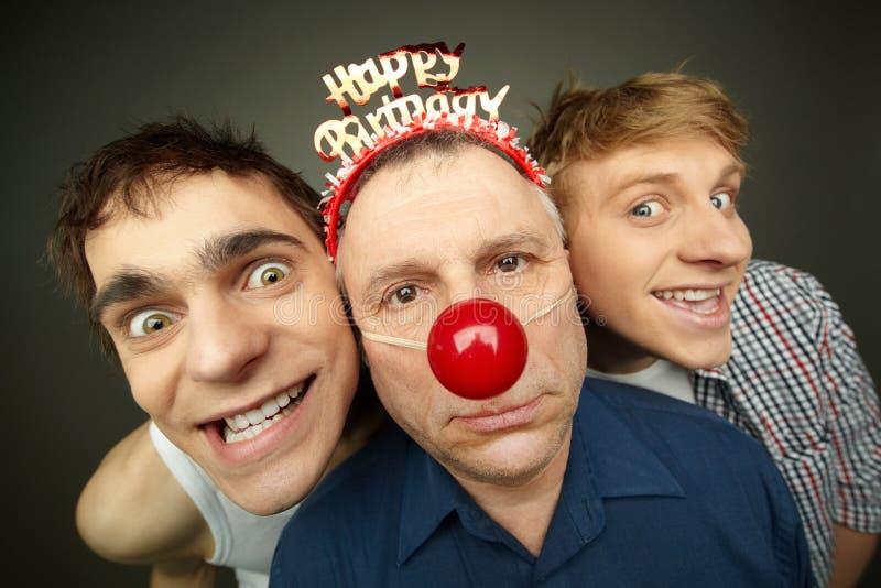 Birthday boy. Two guys having fun playing pranks on a senior men celebrating birthday or fool�s day royalty free stock image